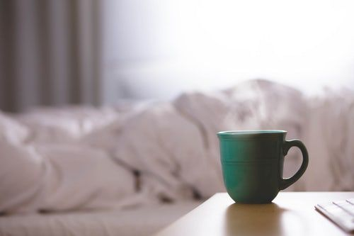 out of focus, rumpled bed in background, green mug on bedside table in foreground to represent blog Let's Talk about Mondays