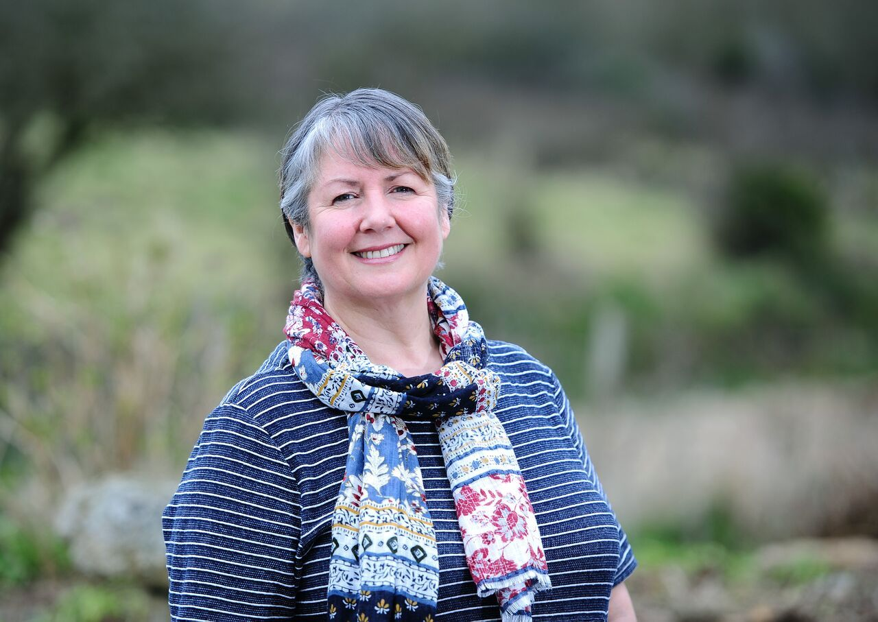 A picture of Fiona Crump from Yellow Dot Women wearing a blue stripey dress and patterned scarf, standing outside in a garden