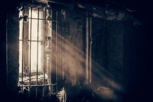 Light streaming in through a barred window into a decaying room. Unconditional Positive Regard