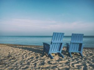 Empathy Two blue wooden chairs sitting on the sand facing out to sea