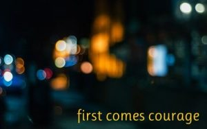First comes courage written against a background of blurred city nightscape