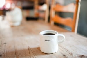 What is coaching and how can it help me blog white mug on table printed with word Begin